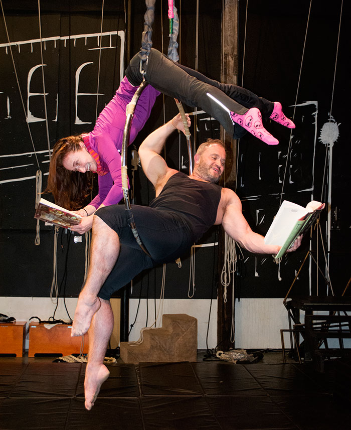 Photo of two members of Canopy reading while performing acrobatics.
