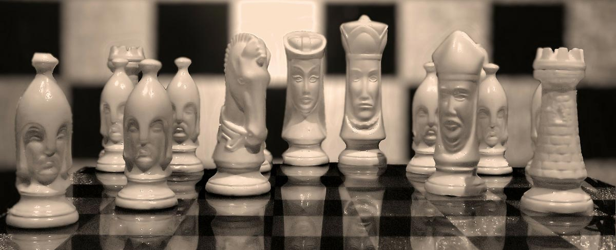 Photo of chess pieces carved to look like people.