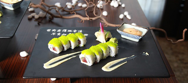 Photo of sushi covered in bright green roe.