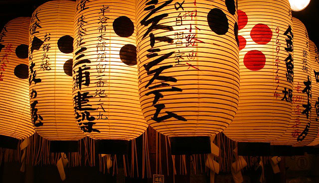 Photo of Japanese paper lanterns glowing at night.