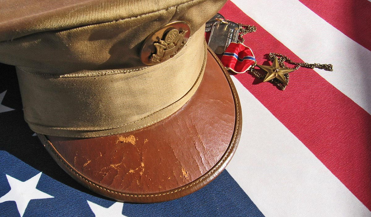 Photo of a military hat and a medal on an American flag.