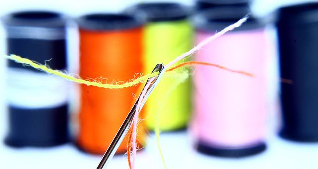 Photo of a needle and many colors of thread.