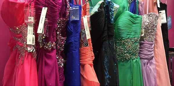 Image of colorful prom dresses hanging on a rack.