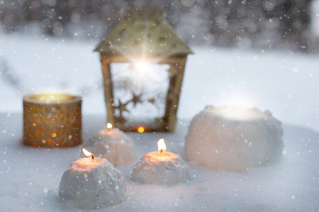 Photo of candles in the snow.