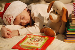 Photo of a little girl who has fallen asleep next to a pile of books.