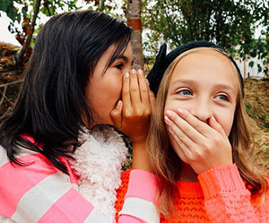 Picture of a teen girl whispering to another
