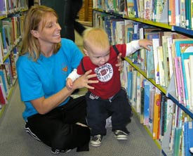 A little boy and his mom are choosing books together.