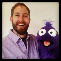 Photo of David Stephens and one of his puppets.