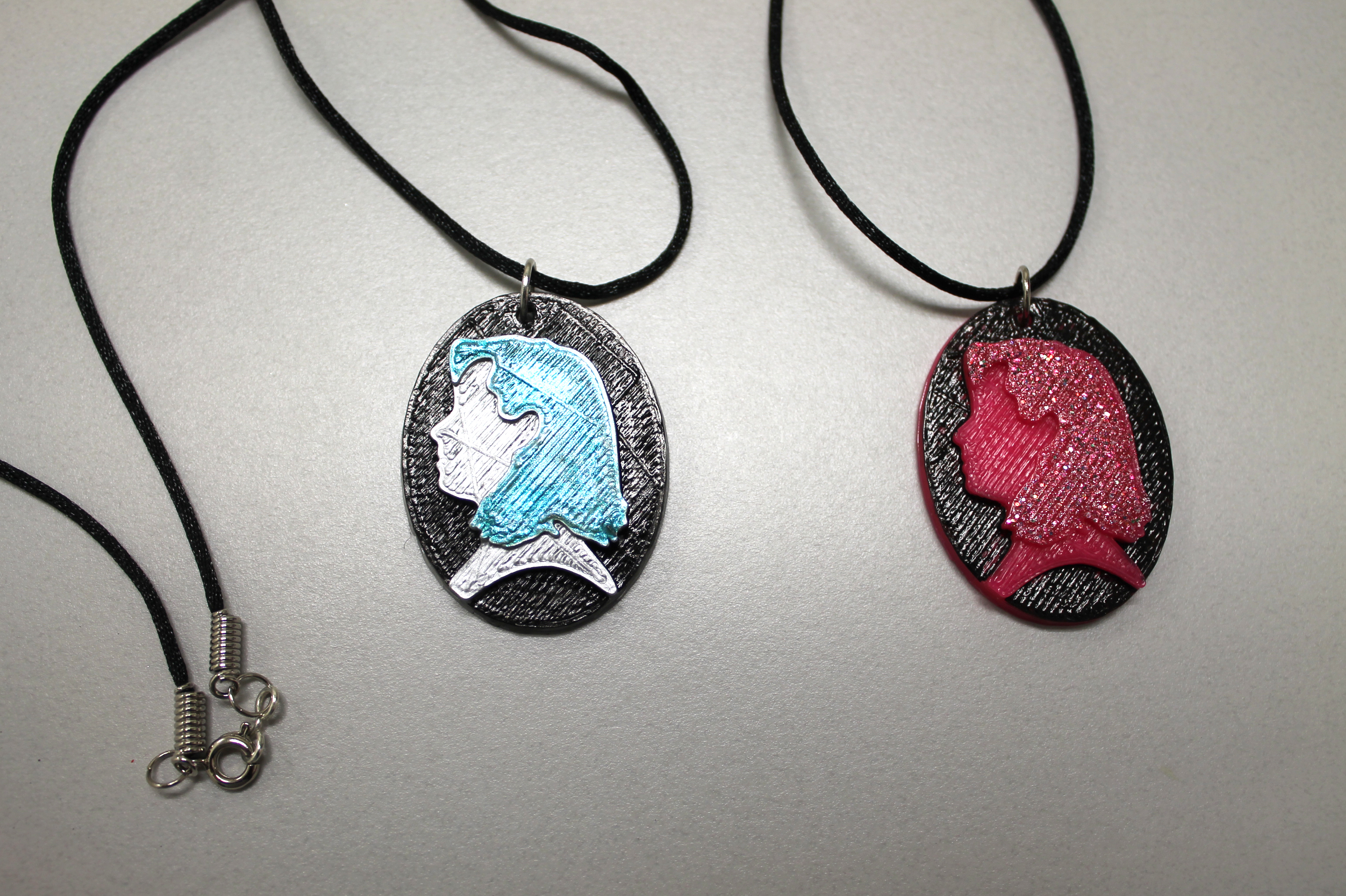 Photo of two custom 3D printed Cameo Pendants.