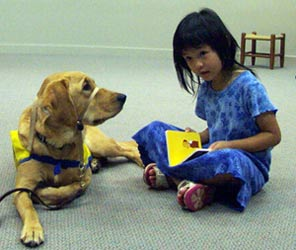 "A photo of a little girl reading to a therapy dog as part of the ""Read to Rover"" program."